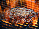 Delicious rib eye steak on a flaming grill
